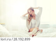 Купить «young woman stretching in bed at home bedroom», фото № 28192899, снято 30 апреля 2016 г. (c) Syda Productions / Фотобанк Лори