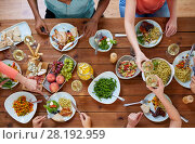 Купить «group of people eating at table with food», фото № 28192959, снято 5 октября 2017 г. (c) Syda Productions / Фотобанк Лори