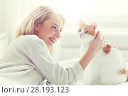 Купить «happy young woman with cat in bed at home», фото № 28193123, снято 30 апреля 2016 г. (c) Syda Productions / Фотобанк Лори