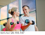 Купить «smiling young woman with personal trainer in gym», фото № 28193147, снято 29 июня 2014 г. (c) Syda Productions / Фотобанк Лори