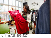 Купить «happy woman choosing dress at clothing store», фото № 28193527, снято 30 ноября 2017 г. (c) Syda Productions / Фотобанк Лори