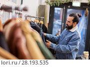 Купить «man choosing clothes at vintage clothing store», фото № 28193535, снято 30 ноября 2017 г. (c) Syda Productions / Фотобанк Лори