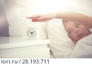Купить «close up of woman with alarm clock in bed at home», фото № 28193711, снято 30 апреля 2016 г. (c) Syda Productions / Фотобанк Лори