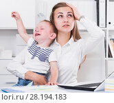 Купить «Mother is working with a naughty child in her arms behind a laptop», фото № 28194183, снято 13 июня 2017 г. (c) Яков Филимонов / Фотобанк Лори