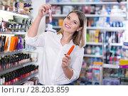 Купить «Young woman choosing mascara in cosmetic shop», фото № 28203859, снято 31 января 2018 г. (c) Яков Филимонов / Фотобанк Лори