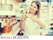 Купить «woman showing a bottle of perfume», фото № 28203875, снято 31 января 2018 г. (c) Яков Филимонов / Фотобанк Лори