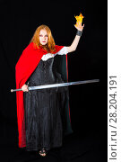 Купить «Young sorceress wearing in a black long gown and red robe standing with longsword and fireball», фото № 28204191, снято 6 июля 2017 г. (c) Сергей Дубров / Фотобанк Лори