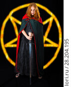 Купить «Young red-haired witch wearing in a black long dress and green robe standing with twohanded sword, on a dark background with fire pentagram», фото № 28204195, снято 6 июля 2017 г. (c) Сергей Дубров / Фотобанк Лори