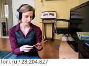 Купить «Tilburg, Netherlands. Young adult caucasian woman enjoying music from her stereo hifi set using a headset and a cd or compact disc.», фото № 28204827, снято 3 марта 2017 г. (c) age Fotostock / Фотобанк Лори