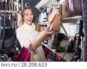 Купить «Excited young female selecting new handbag», фото № 28208623, снято 19 января 2019 г. (c) Яков Филимонов / Фотобанк Лори