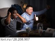 Купить «Two friends supporting different teams», фото № 28208907, снято 26 февраля 2018 г. (c) Яков Филимонов / Фотобанк Лори