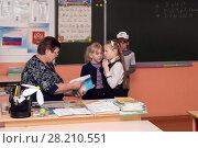 Учитель проверяет тетрадь у школьницы, которая волнуется (2018 год). Редакционное фото, фотограф Светлана Попова / Фотобанк Лори