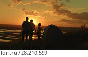 Купить «Young happy healthy family - father, mom and son in camping - stands on high hill at summer sunset and looking to horizont», видеоролик № 28210599, снято 24 апреля 2018 г. (c) Константин Шишкин / Фотобанк Лори