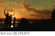 Купить «Young family - father, mom and son in camping - stands on high hill at summer sunset and have happy, silhouette», видеоролик № 28210611, снято 24 апреля 2018 г. (c) Константин Шишкин / Фотобанк Лори