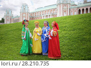 Купить «MOSCOW - JUN 06, 2015: Four women in colorful Russian folk costumes sing on the green lawn in front of the manor at the festival of fire and rescue service in Tsaritsyno», фото № 28210735, снято 6 июня 2015 г. (c) Losevsky Pavel / Фотобанк Лори