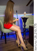 Купить «Beautiful girl in red dress sitting in the hookah room», фото № 28210775, снято 22 апреля 2015 г. (c) Losevsky Pavel / Фотобанк Лори