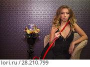 Купить «Beautiful girl in black dress with decollete in the hookah room», фото № 28210799, снято 22 апреля 2015 г. (c) Losevsky Pavel / Фотобанк Лори