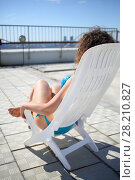 Купить «Woman with curly hair in a blue swimsuit sunbathing in a lounger on the roof of a multistory building, view from the back», фото № 28210827, снято 8 июня 2015 г. (c) Losevsky Pavel / Фотобанк Лори
