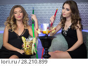 Купить «Two beautiful young women resting in the hookah room, focus on the right girl», фото № 28210899, снято 22 апреля 2015 г. (c) Losevsky Pavel / Фотобанк Лори
