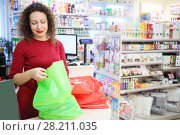 Купить «Pretty smiling woman in red packs purchase in Goods for Home shop», фото № 28211035, снято 14 октября 2016 г. (c) Losevsky Pavel / Фотобанк Лори