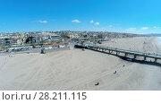 Купить «MANHATTAN BEACH - NOV 02, 2014: People walk by Manhattan Beach with long pier at autumn sunny day. Aerial view. Pier is 928 feet long.», фото № 28211115, снято 2 ноября 2014 г. (c) Losevsky Pavel / Фотобанк Лори