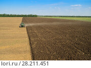 Купить «KRASNODAR REGION, RUSSIA - AUG 19, 2015: Modern tractor plows big field, In 2015 in Krasnodar region yields reached record level - 58.4 centners per hectare», фото № 28211451, снято 19 августа 2015 г. (c) Losevsky Pavel / Фотобанк Лори