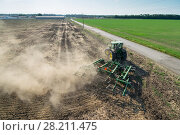 Купить «KRASNODAR REGION, RUSSIA - AUG 19, 2015: Modern tractor plows field after harvesting, In 2015 in Krasnodar region yields reached record level - 58.4 centners per hectar», фото № 28211475, снято 19 августа 2015 г. (c) Losevsky Pavel / Фотобанк Лори