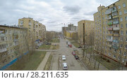 Купить «MOSCOW - APR 22, 2015: Cars are parked on street under construction near dwelling houses at spring cloudy day. Aerial view video frame», фото № 28211635, снято 22 апреля 2015 г. (c) Losevsky Pavel / Фотобанк Лори