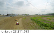 Купить «SAMARA - MAY 24, 2015: Three small racing cars ride by ground track under electricity wires at spring sunny day. Aerial view video frame», фото № 28211695, снято 24 мая 2015 г. (c) Losevsky Pavel / Фотобанк Лори
