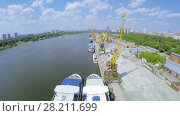 Купить «MOSCOW - JUN 03, 2015: Several vessels and cranes in city river port at summer sunny day. Aerial view videoframe», фото № 28211699, снято 3 июня 2015 г. (c) Losevsky Pavel / Фотобанк Лори