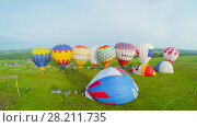 Купить «PERESLAVL ZALESSKY - JUL 18, 2015: Several colourful air balloons on field before fly at summer sunny day in Pereslavl Zalessky. Aerial view videoframe», фото № 28211735, снято 18 июля 2015 г. (c) Losevsky Pavel / Фотобанк Лори