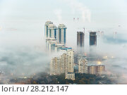 Купить «MOSCOW, RUSSIA - SEP 26, 2014: Residential complex Sparrow Hills (Vorobyovy Gory) and construction site of residential complex Dolina Setun in morning fog», фото № 28212147, снято 26 сентября 2014 г. (c) Losevsky Pavel / Фотобанк Лори