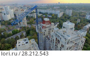 Купить «MOSCOW - SEP 15, 2015: Crane above building site of residential complex Falcon Fort at autumn evening. Aerial view videoframe», фото № 28212543, снято 15 сентября 2015 г. (c) Losevsky Pavel / Фотобанк Лори