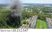 Купить «MOSCOW - JUL 25, 2015: Fire with dark smoke at summer sunny day in New Town neighborhood. Aerial view», фото № 28212547, снято 25 июля 2015 г. (c) Losevsky Pavel / Фотобанк Лори