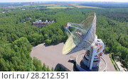 Купить «MOSCOW - JUL 25, 2015: Antenna TNA 1500 of radio telescope RT-64 Bear Lakes among forest and cityscape on horizon at summer sunny day. Aerial view», фото № 28212551, снято 25 июля 2015 г. (c) Losevsky Pavel / Фотобанк Лори