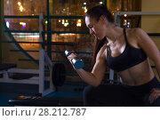 Купить «Woman lifting dumbbells in the gym», фото № 28212787, снято 21 марта 2018 г. (c) Владимир Мельников / Фотобанк Лори