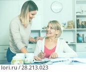 Купить «Daughter helps mother to lead home accounting», фото № 28213023, снято 13 ноября 2017 г. (c) Яков Филимонов / Фотобанк Лори
