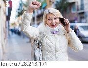 Купить «Female talking on mobile phone outdoor and raise hand up», фото № 28213171, снято 21 декабря 2017 г. (c) Яков Филимонов / Фотобанк Лори
