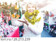 Купить «Woman is preparing for Christmas and choosing wreath for her house», фото № 28213239, снято 21 декабря 2017 г. (c) Яков Филимонов / Фотобанк Лори