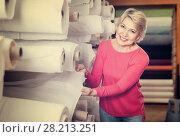Купить «Mature female shopper searching for suitable fabric», фото № 28213251, снято 15 февраля 2017 г. (c) Яков Филимонов / Фотобанк Лори