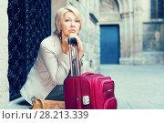 Купить «Adult woman 50s years old is sitting with suitcase», фото № 28213339, снято 3 сентября 2017 г. (c) Яков Филимонов / Фотобанк Лори