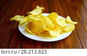 Купить «Crispy potato chips in a white plate», видеоролик № 28213823, снято 12 марта 2018 г. (c) Peredniankina / Фотобанк Лори