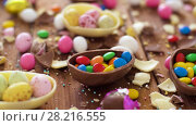 Купить «chocolate easter eggs and drop candies on table», видеоролик № 28216555, снято 16 марта 2018 г. (c) Syda Productions / Фотобанк Лори