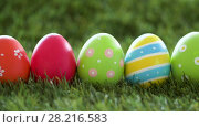 Купить «row of colored easter eggs on artificial grass», видеоролик № 28216583, снято 15 марта 2018 г. (c) Syda Productions / Фотобанк Лори