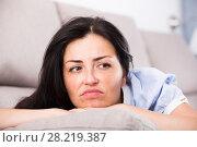 Купить «Young sad woman lying on cozy sofa», фото № 28219387, снято 2 июня 2017 г. (c) Яков Филимонов / Фотобанк Лори