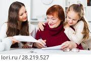 Купить «Smiling senior woman with family writing papers», фото № 28219527, снято 25 ноября 2017 г. (c) Яков Филимонов / Фотобанк Лори