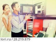 Купить «Smiling family couple choosing new microwave», фото № 28219879, снято 15 июня 2017 г. (c) Яков Филимонов / Фотобанк Лори