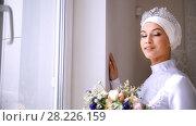 Купить «Beautiful muslim bride with make up looks out the window and smiles», видеоролик № 28226159, снято 22 июля 2019 г. (c) Константин Шишкин / Фотобанк Лори