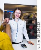 Купить «Woman seller is handing numerous purchases to client», фото № 28226723, снято 20 марта 2017 г. (c) Яков Филимонов / Фотобанк Лори
