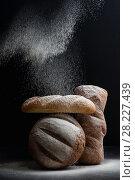 Купить «Freshly baked different bread on a black background, on which flour is poured.», фото № 28227439, снято 21 марта 2018 г. (c) Olesya Tseytlin / Фотобанк Лори